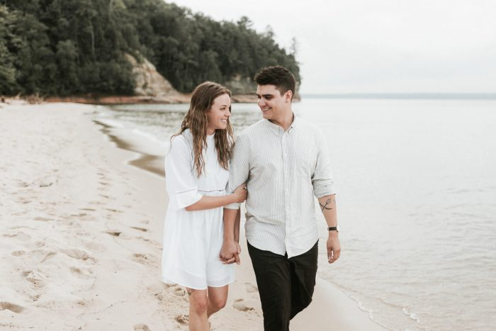 An engaged couple pose for their Lake Superior beach engagement photos. Photographed by Northern Michigan Wedding Photographer Farrah Julin.