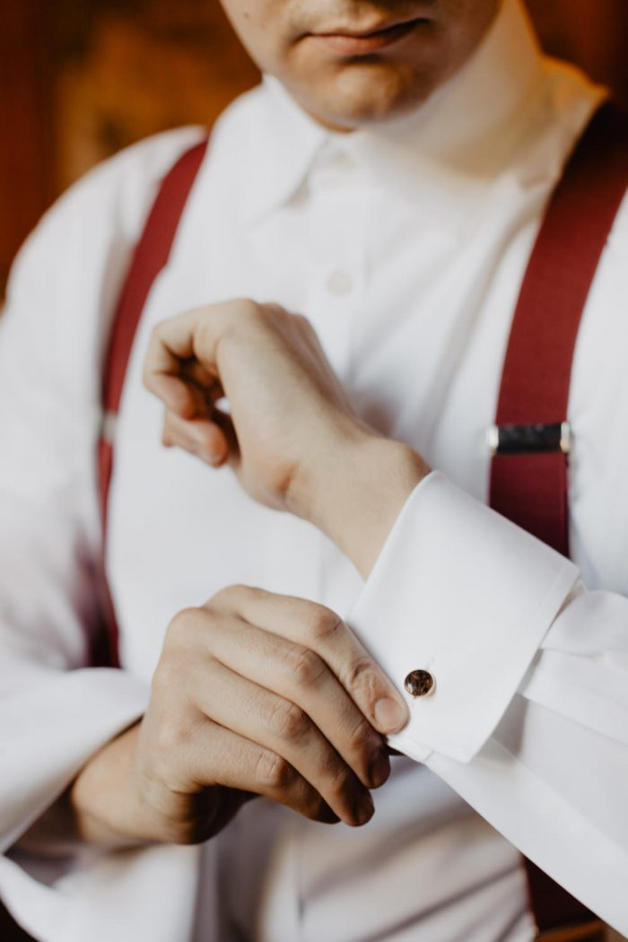 Groom puts on cuff links for his wedding at Spillian in upstate New York. Yellow wedding shoes next to a bridal bouquet photo. Photographed by New York Wedding Photographer Farrah Julin.