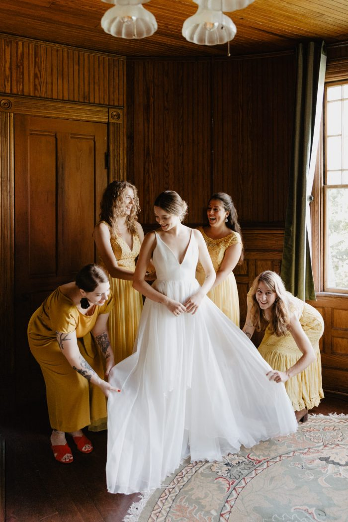 Photo of bridesmaids in yellow dresses help the bride get ready for her Catskill Mountain Wedding. Groom gets ready for his wedding at Spillian in Fleischmanns, New York. Photographed by New York wedding photographer Farrah Julin.