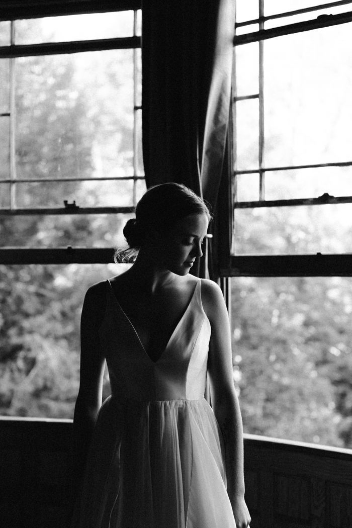 Bride looks out a window during her wedding at Spillian in Fleishmanns, NY. Groom gets ready for his wedding at Spillian in Fleischmanns, New York. Photographed by New York wedding photographer Farrah Julin.