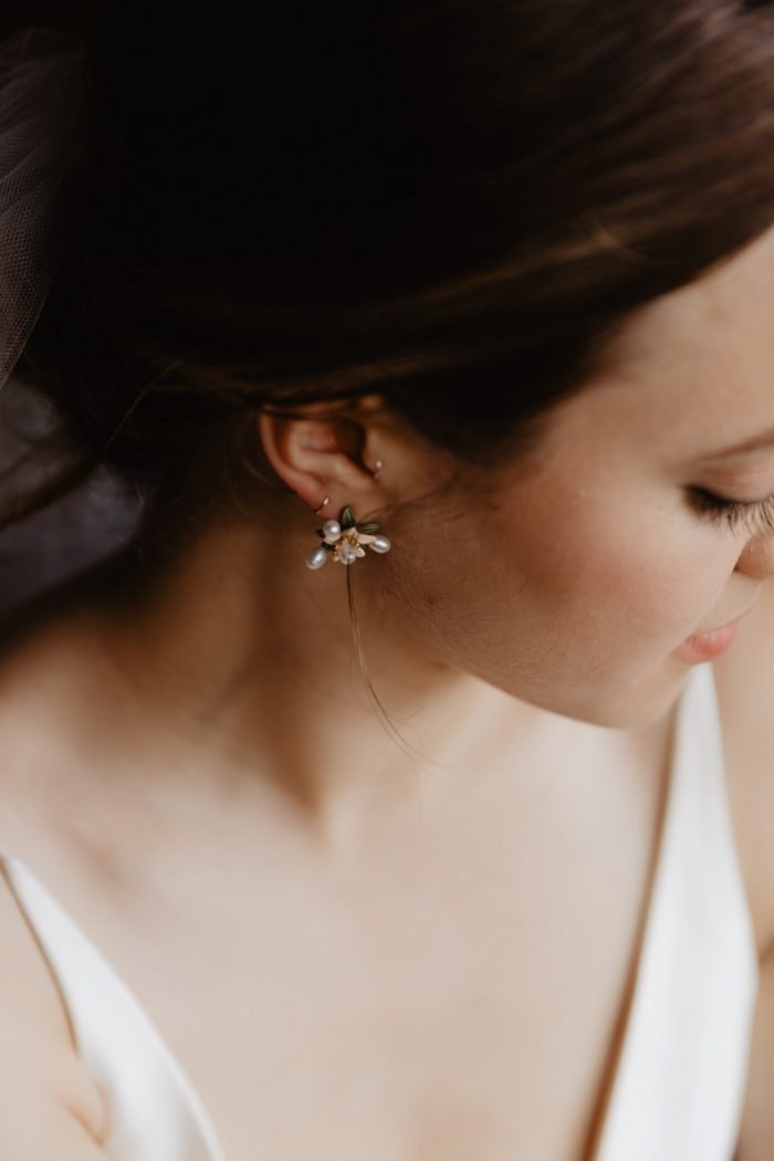Bride wears a flower earring to her wedding at Spillian. Groom gets ready for his wedding at Spillian in Fleischmanns, New York. Photographed by New York wedding photographer Farrah Julin.