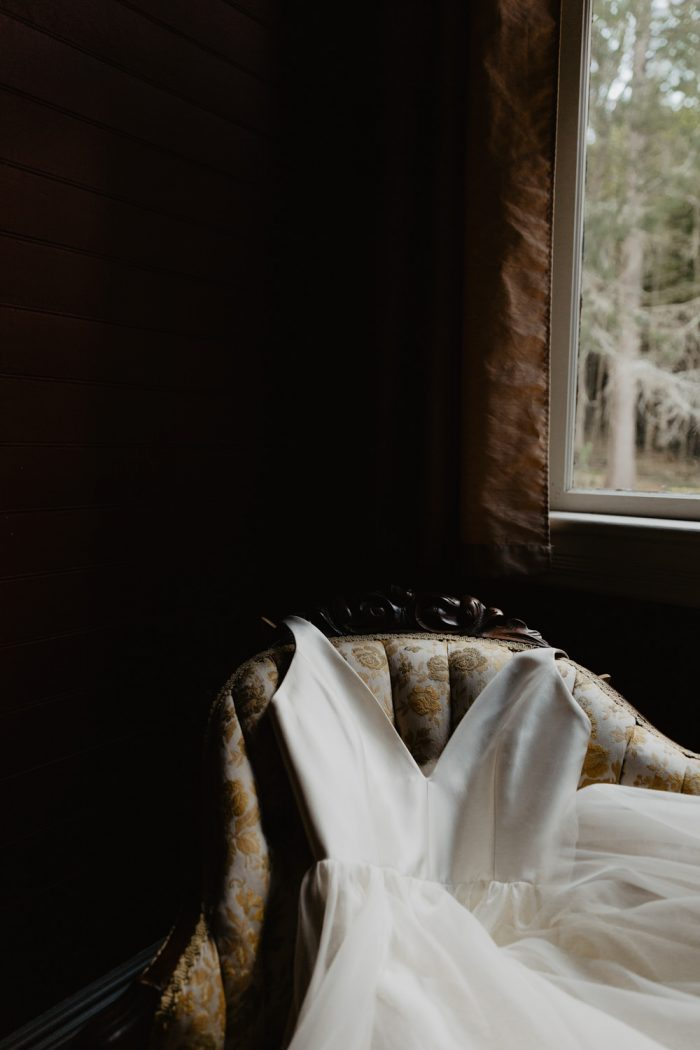 Photo of a Leanne Marshall wedding dress laid out on a bench at Spillian in the Catskill Mountains.